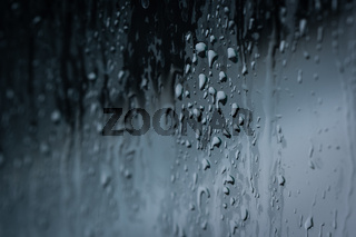 Close up of splashes of water and waterdrops running down on glass panel of bathtub in bathroom while taking a shower