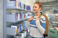 teenage student girl with school bag at library