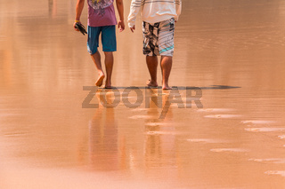 Two Men Walking on the Wet Sand