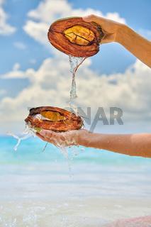 Woman splashing water with coconut on beach