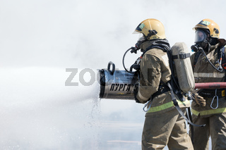 Two firefighters extinguish fire from fire hose, using firefighting water-foam barrel with air-mechanical foam during professional