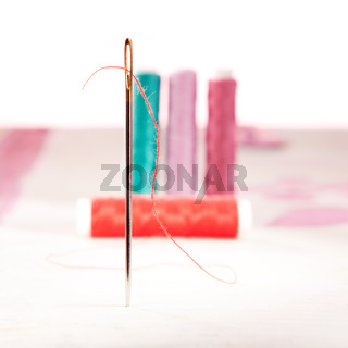 Standing sewing needle with red thread