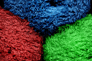 Colored tkan in rolls with a steep plan. Multi-colored rag with a long pile. Abstract background of manufactory