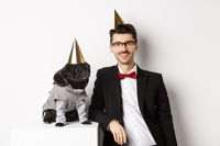 Image of handsome young man celebrating birthday with cute black pug in party costume and cone on head, standing over white background