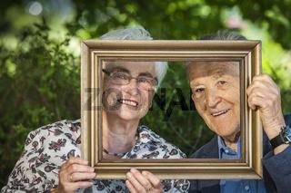 Retired couple hold a frame frame