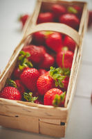 Fresh healthy strawberries in a wooden box on white background.
