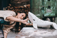 Portrait of young woman carefully work on a ceramic whale in workshop.