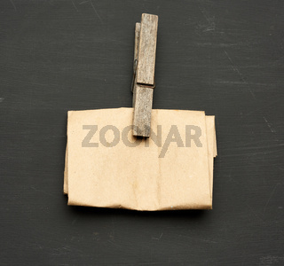 a piece of brown paper and a wooden clothespin