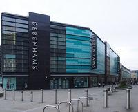 People walking past Debenhams department store near Broadway shopping center in Bradford