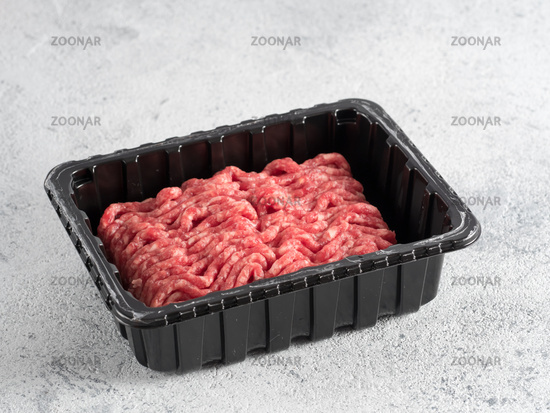 raw minced beef on light gray cement background