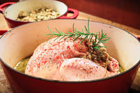 Side view of a raw chicken with stuffing in a pot