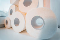 Toilet paper shortage concept with stacked rolls.