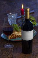 Weinflasche und Lasagne auf Holz
