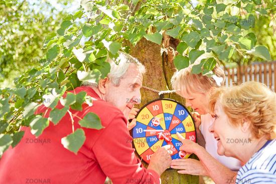 Senioren an der Dartscheibe beim Punkte zählen
