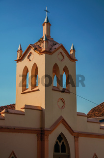 Facade of small church and belfry at sunset