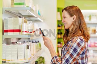 Frau fotografiert Barcode in Drogerie