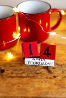 Two cups of coffee in red cups on a background of garlands. Postcard with date and month. Morning surprise for Valentine's Day. View from above.