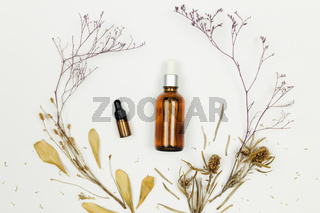 Bottles of cosmetic oil with dried herbs on white background