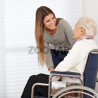 Frau redet mit Seniorin im Rollstuhl