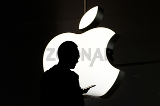 Silhouette of a person using mobile phone in front of the Apple logo