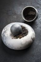 Modern design minimalistic mortar with black pepper berries as closeup on a rustic board