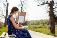 Young female artist painting picture in spring park.