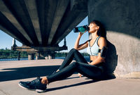 Young fitness woman drinking water from bottle