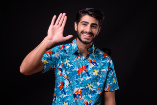 Young handsome bearded Persian tourist man ready for vacation against black background