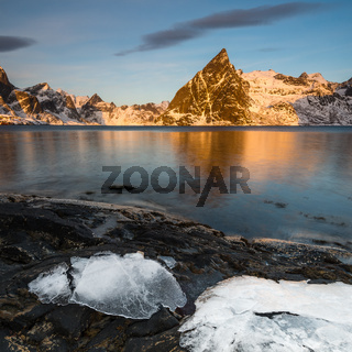 Ice sheets on dark rock with lake and snow-clad steep mountains in the Reinefjord on the Lofoten islands in Norway in golden morning light on clear winter day