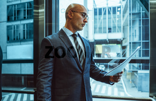 Serious Businessman reads holding paper document. Middle aged Caucasian examines content of business contract standing against of modern building outside the window. Side view