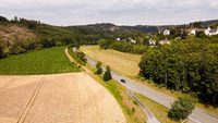Rural road near a small village with a car - drone or aerial view