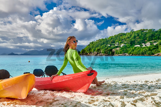 Woman sitting on kayak at beach, Seychelles, Mahe