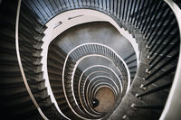 looking deep into long spiral stair case of big building