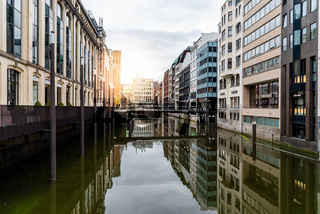 Scenic view of Bleichenfleet canal in Hamburg with luxury fashion stores reflection on water with sunflare