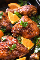 appetizing slices of baked chicken with crispy fried crust and oranges in a baking sheet