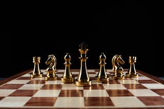 Golden chess figures standing on chessboard