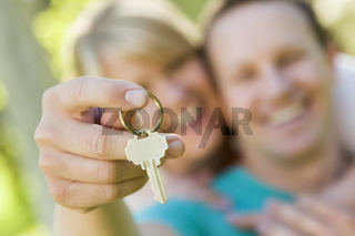 Happy Couple Holding Blank House Key Outside