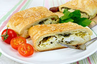 Roll filled with spinach and cheese in bowl on tablecloth