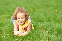 Mädchen liegt auf Wiese im Frühling