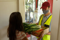 Caucasian woman taking food box from delivery man wearing face mask at front door