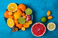 Summer and citrus fruits in bowl on blue background.  Healthy eating concept.