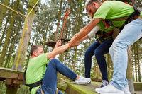 Team hilft Mann beim Klettern im Kletterwald