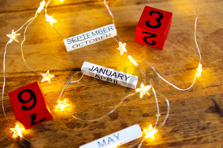 Perpetual calendar on a wooden table, different months and dates on the background of garlands in the form of a star.