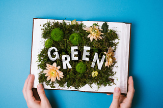 Flatlay of woman's hands holding an open book with green moss, flowers and greenery inside with white cut out words 'GREEN' on blue background