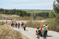 SUDBURY, ONTARIO, CANADA - MAY 21 2009: Group of workers and geologists in hardhats and high-visibility vests walking on road to geological outcrop site.