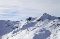 Snowy off piste ski slope at high winter mountains and sunlit cloudy sky