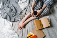 Flatlay of woman with a cup of black tea and craft paper notebook in a bed, selective focus