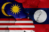 flags of Malaysia and Laos painted on cracked wall