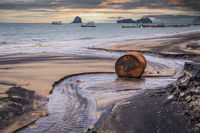 Old rusty barrel oil on beach in Asia on sunset