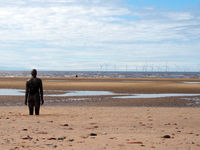 statue of anthony gormley another place installation on the beach at seffton in southport with the wind turbines at burbo bank in the distance